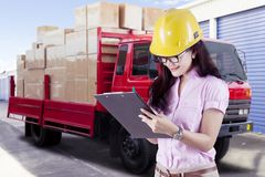 Female supervisor with safety helmet looking through checklist in front of truck carrying boxes Royalty Free Stock Image
