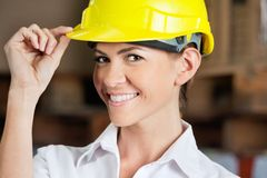 Female Supervisor Touching Hardhat At Warehouse Royalty Free Stock Photography