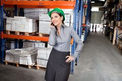 Female Supervisor Using Cell Phone At Warehouse Stock Photos