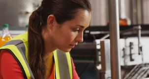 Female supervisor using digital tablet near production line stock footage