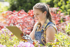 Female supervisor writing on clipboard in garden Royalty Free Stock Images