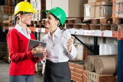 Female Supervisors Discussing Work At Warehouse. Two female supervisors with digital tablet discussing work at warehouse Stock Photography