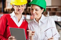 Female Supervisors Using Digital Tablet At. Two female supervisors using digital tablet in warehouse Royalty Free Stock Photo