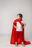 Female superwoman kid in super hero costume. Female superwoman kid posing in studio in super hero costume royalty free stock photo