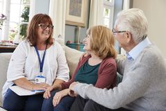 Female Support Worker Visits Senior Couple At Home royalty free stock image