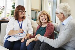 Female Support Worker Visits Senior Couple At Home royalty free stock photography