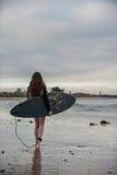 Female surf girl on dawn patrol. Stock Photos