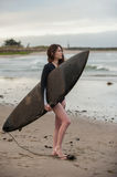 Female surf girl looking at small waves. Stock Image