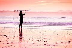 Female surfer. On the beach at the sunset Royalty Free Stock Images