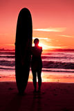 Female surfer. On the beach at the sunset Stock Photos