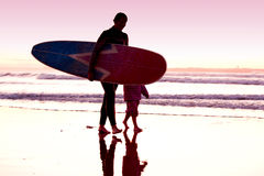 Female surfer. And her daughter walking in the beach at the sunset Royalty Free Stock Image
