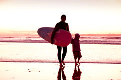 Female surfer. And her daughter walking in the beach at the sunset Stock Images