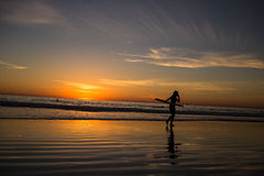 Female surfer at beach sunset. Silhouette of a female surfer holding a surfboard walking out of the ocean at sunset Stock Photo