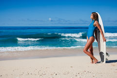 Female surfer in blue swimwear with board in hands on coastline. Attractive blonde female surfer with board in hands on tropical coastline with blue deep water Stock Photo