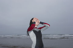 Female Surfer With Head In Hands At Beach. Beautiful female surfer with head in hands at beach Royalty Free Stock Images