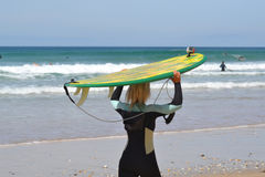 Female surfer heading towards the waves. Female surfer holding a surfboard over her head Royalty Free Stock Images