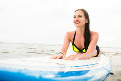 Female surfer paddling on surfboard to the open sea Stock Photography