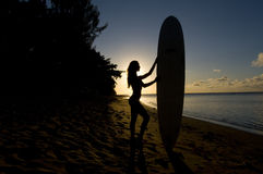 Female surfer silhouette. Silhouette of a woman standing on the beach with a surfing board Stock Images