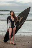 Female surfer in spring wetsuit. Sexy California surfer girl holding board with wetsuit top unzipped looking to right Stock Photos