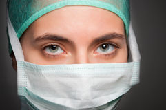 Female Surgeon. Closeup portrait of a female surgeon, with face mask, in a dark grey background Stock Photo