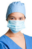 Female Surgeon. Young female surgeon with scrubs, holding a face mask on a white background Stock Photo