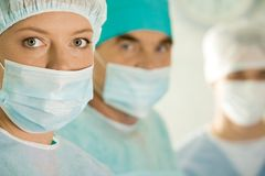 Female surgeon. Portrait of female surgeon wearing protective mask on background of her colleagues Stock Photography
