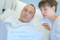 Female surgeon asking male patient several questions stock image
