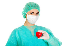 Female surgeon doctor holding heart. Smiling female surgeon doctor with heart royalty free stock images