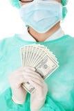 Female surgeon doctor holding money Royalty Free Stock Photos