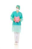 Female surgeon doctor holding piggy bank.  Royalty Free Stock Photo