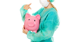 Female surgeon doctor holding piggy bank.  Stock Photo