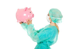 Female surgeon doctor holding piggy bank Royalty Free Stock Images
