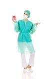 Female surgeon doctor holding piggy bank.  Royalty Free Stock Image
