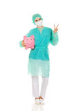 Female surgeon doctor with piggy bank shows victory sign Royalty Free Stock Photography