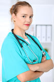 Female surgeon doctor is standing with arms crossed and smiling at hospital.  Physician ready to examine patient. Female surgeon doctor is standing with arms Stock Photos
