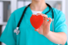 Female surgeon doctor with stethoscope holding heart. Female surgeon doctor with stethoscope holding heart stock image