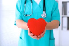 Female surgeon doctor with stethoscope holding heart. Female surgeon doctor with stethoscope holding heart stock images