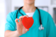 Female surgeon doctor with stethoscope holding heart. Female surgeon doctor with stethoscope holding heart stock photography