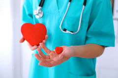 Female surgeon doctor with stethoscope holding heart. Female surgeon doctor with stethoscope holding heart royalty free stock photos