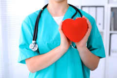 Female surgeon doctor with stethoscope holding heart. Female surgeon doctor with stethoscope holding heart royalty free stock photo