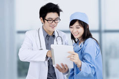 Female surgeon and doctor use tablet Stock Image