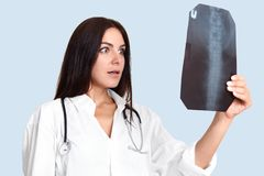 Female surgeon examines X ray, looks at backbone, shocked with result. Woman radiologist in white medical rope finds out cancer, s. Urprised with progress of royalty free stock photography