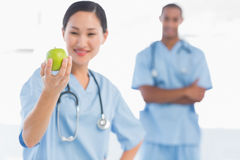 Female surgeon holding an apple with colleague in hospital Royalty Free Stock Photos