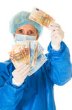 Female surgeon holding banknotes Royalty Free Stock Images
