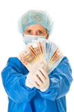 Female Surgeon Holding Banknotes Royalty Free Stock Image