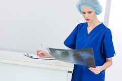 Female surgeon in medical cap looking at x-ray and writing diagnosis. In hospital stock image