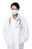 Female surgeon posing with hands in lab coat Royalty Free Stock Images
