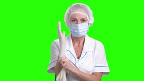 Female surgeon putting on protective gloves. Female doctor wearing protective hat and mask putting on white sterilized surgical gloves on Alpha Channel stock video footage