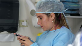 Female surgeon reading message at mobile phone stock video footage