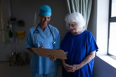 Female surgeon showing a medical report to a senior female patient in a hospital room. Front view of a Caucasian female surgeon showing medical report to a royalty free stock images